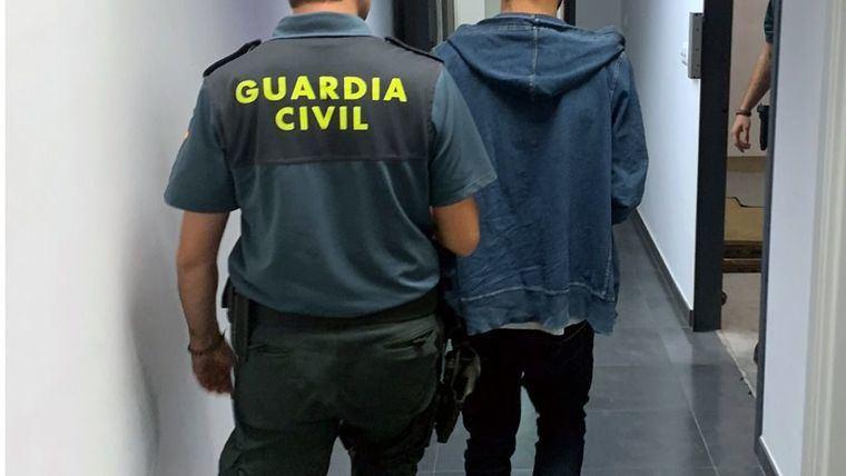 Un guardia civil conduce a un detenido en otra operación policial